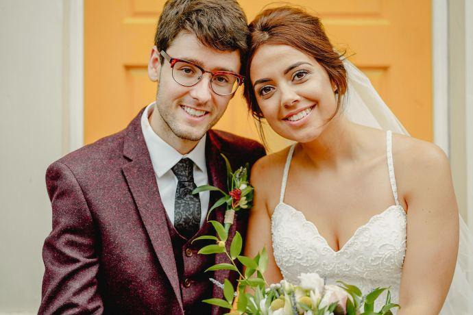 bride and groom portrait in front of yellow door