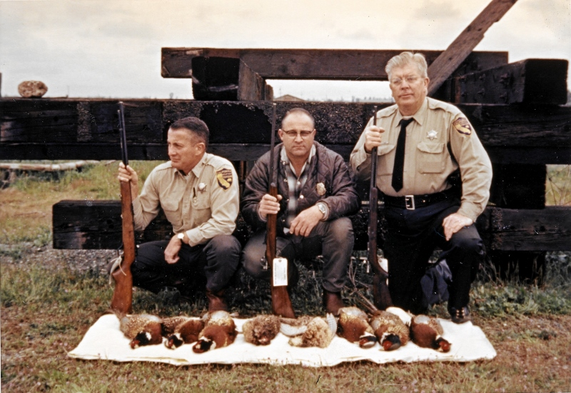 Pictured, left to right, are Warden Wally Callan, U.S. Fish and Wildlife Agent Bob Norris, and Warden Harold Erwick, circa 1965, with evidence seized during a pheasant case. Photo courtesy of Steven T. Callan.