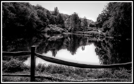 A black and white photo overlooking the lake with a fence at the front