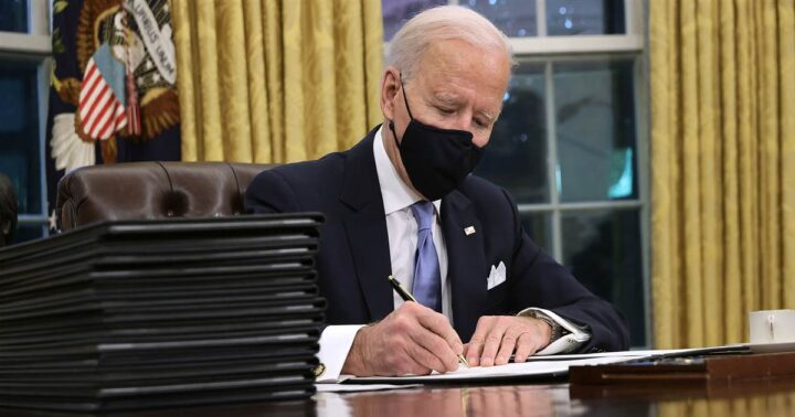 Biden clone in fake Oval Office at Amazon studios signing fake Executive Orders that are blank, with attached ear lobes.