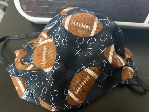 Football face mask a face mask with footballs and game plays on it. #football
