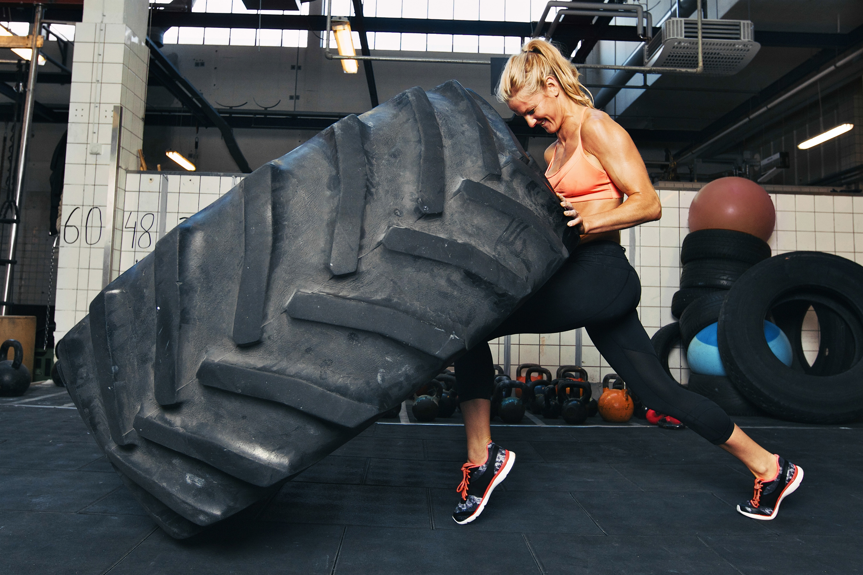 Woman Flipping a Huge Tire at the Gym