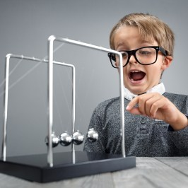 Boy Doing Experiment With Newton Cradle
