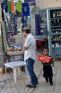 Kid selling bags of popcorn to tourists