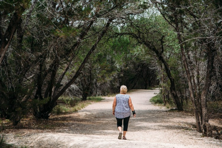 Stevie's mom walking under a canopy of trees at Pedernales Falls State Park outside of Austin Texas