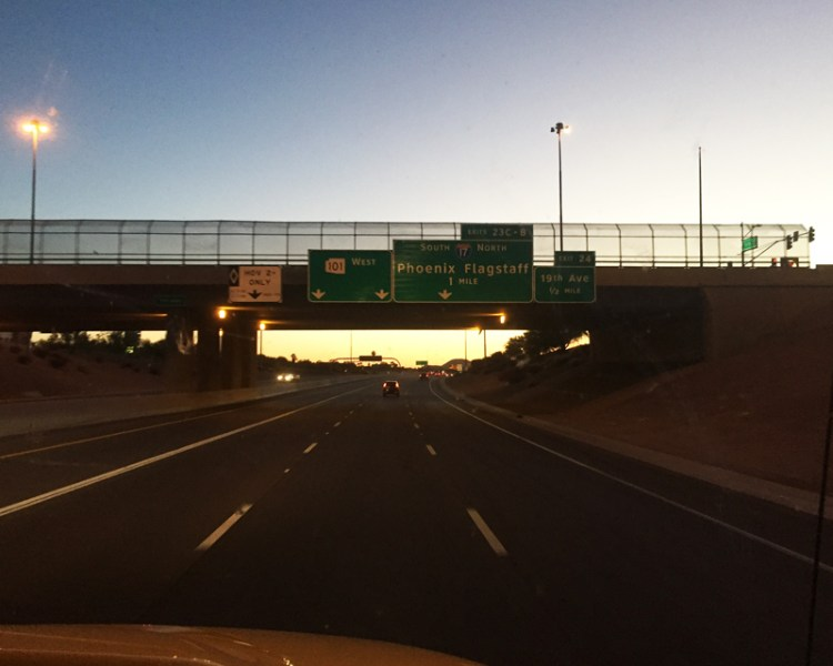 Photo of a road highway in Phoenix, Arizona with a road sign to Phoenix and Flagstaff at night time.