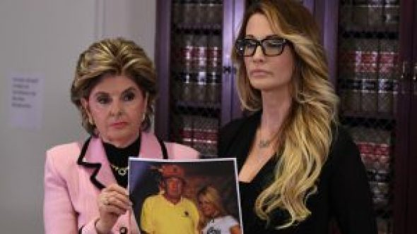 Jessica Drake (R), who works for an adult film company, stands with a photo of her meeting with Donald Trump, beside attorney Gloria Allred as they talk about allegations of sexual misconduct against the Republican presidential hopeful during a press conference in Los Angeles on October 22, 2016.  / AFP PHOTO / Mark RALSTON