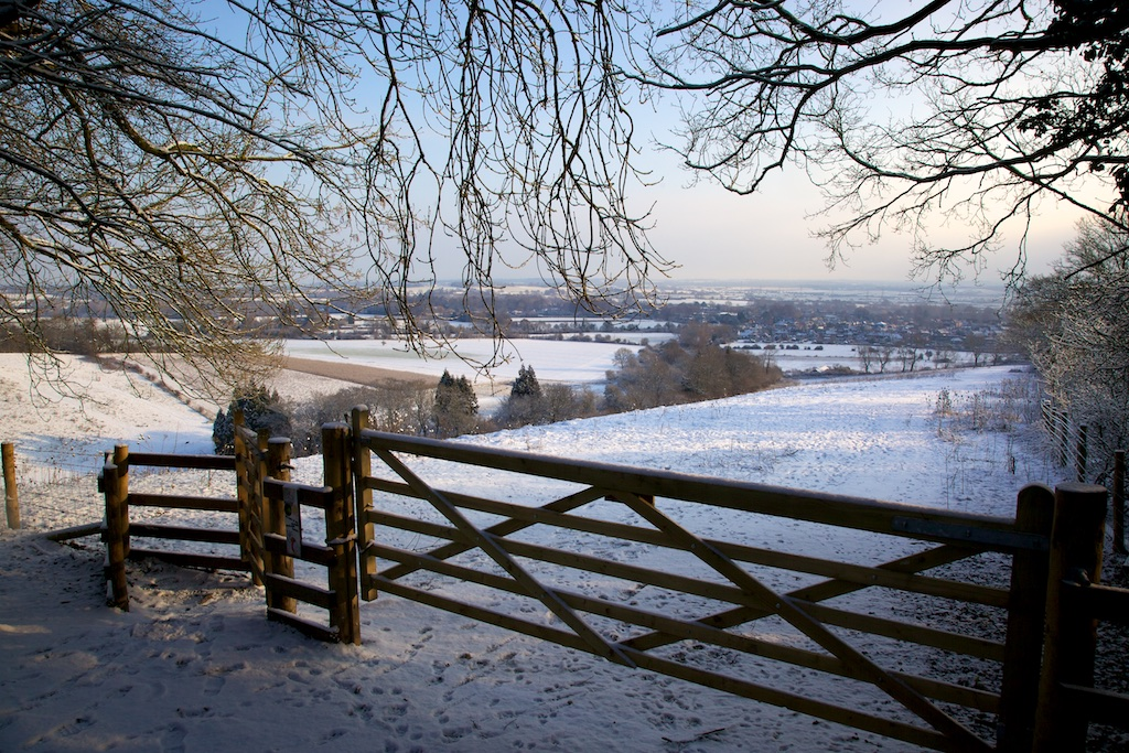 Snowy Downland view with a gate and fields