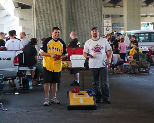 Pittsburgh Pirates and New York Mets fans playing cornhole game