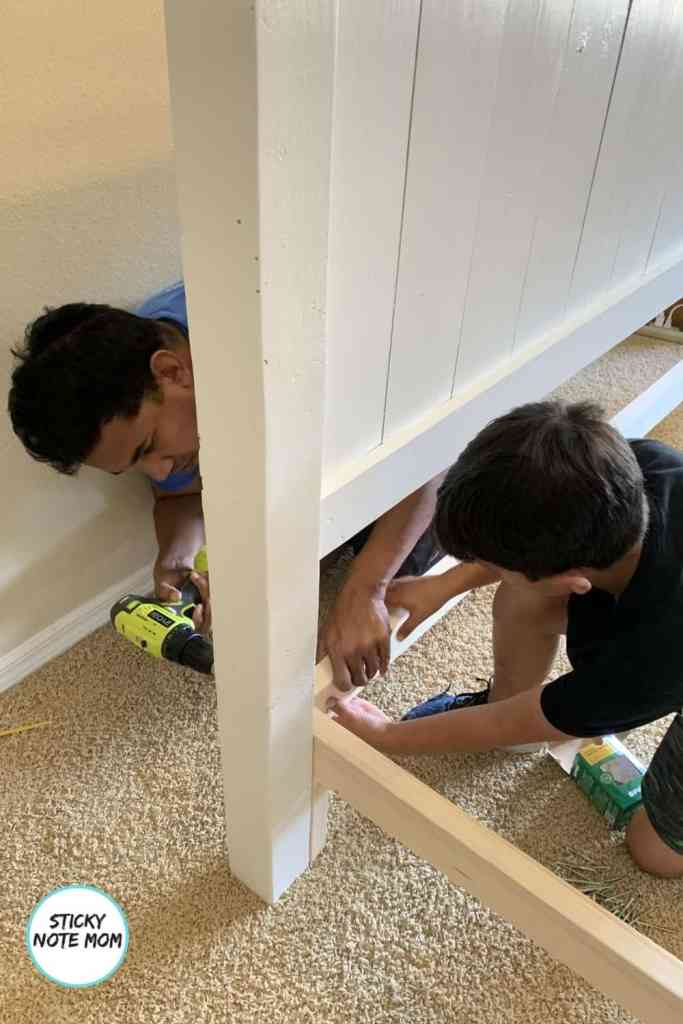 Father son screwing headboard and side rails together