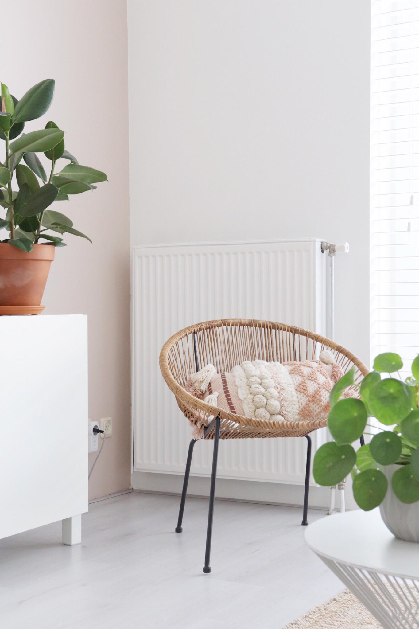 een hoekje in de woonkamer met een rotan stoel, roze accent en twee groene planten.