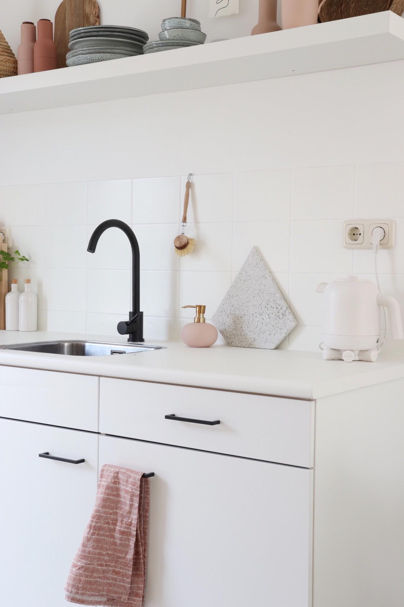 Witte keuken met roze en zwarte accenten na de keuken make-over