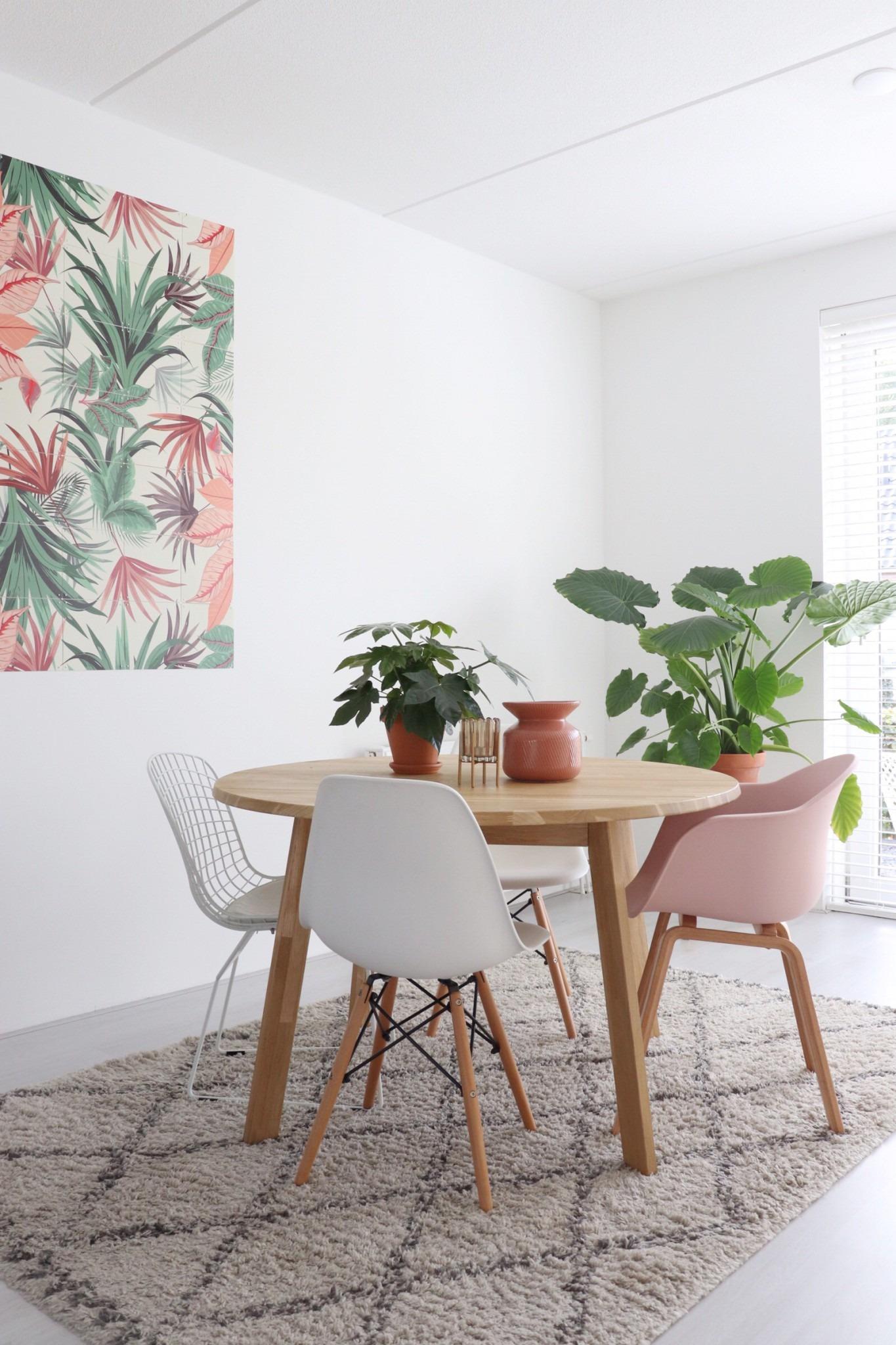 De eethoek met een ronde tafel, IXXI en grote planten. Binnenkijken in een huis in Ochten