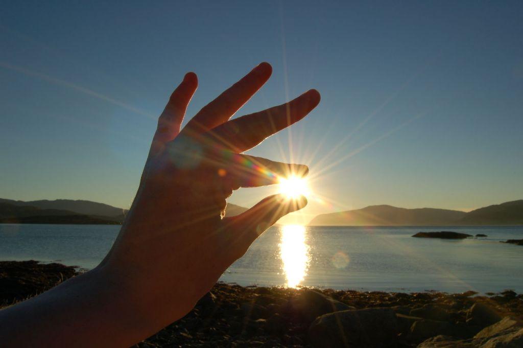 Midnattssolen lyser opp mellom fingrene på en utstrakt hånd.