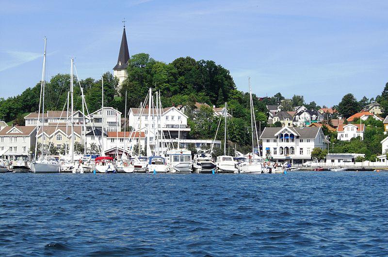 Mange båter i Grimstad gjestehavn med blå himmel og blått hav. Grimstad kirke i bakgrunnen.