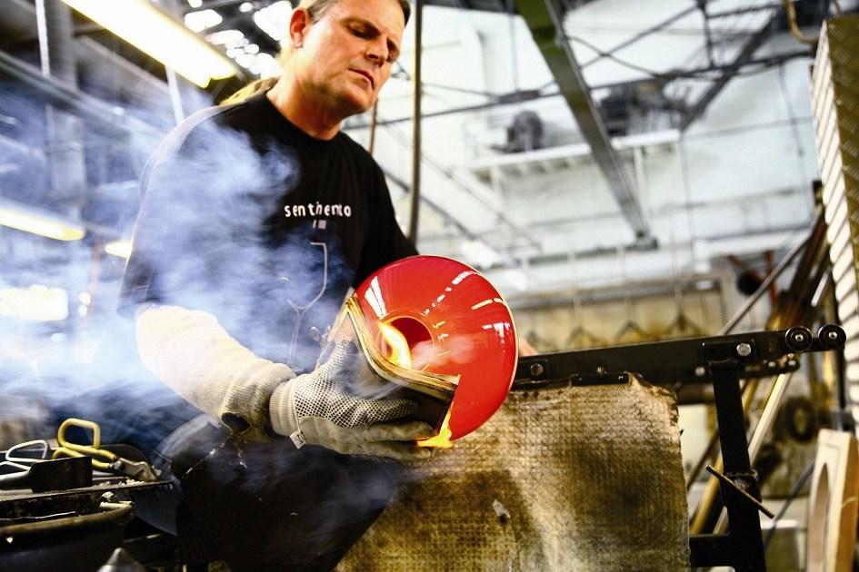 En mann i full sving med å blåse et glass på Hadeland Glassverk.