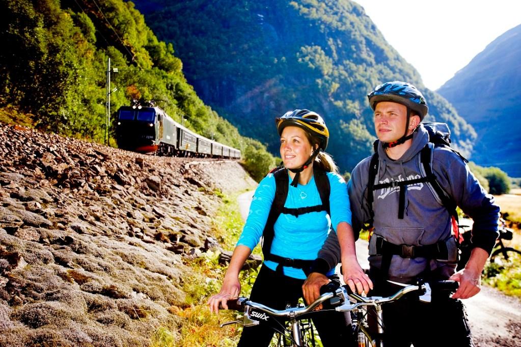 Et ungt par har syklet Rallarvegen og besundrer naturen i Flåmsdalen. Flåmsbana kommer kjørende ved siden av.