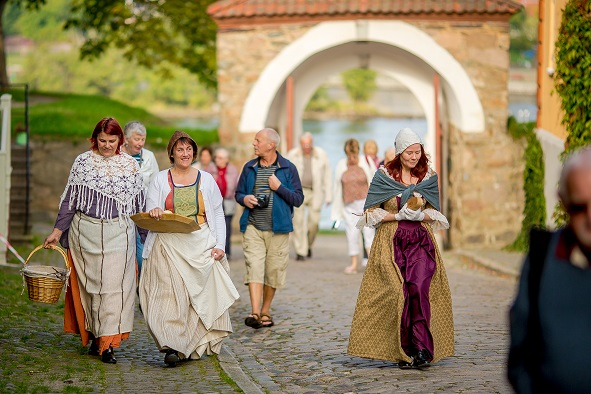 Mennesker i gamle folkedrakter går i Gamlebyen i Fredrikstad.