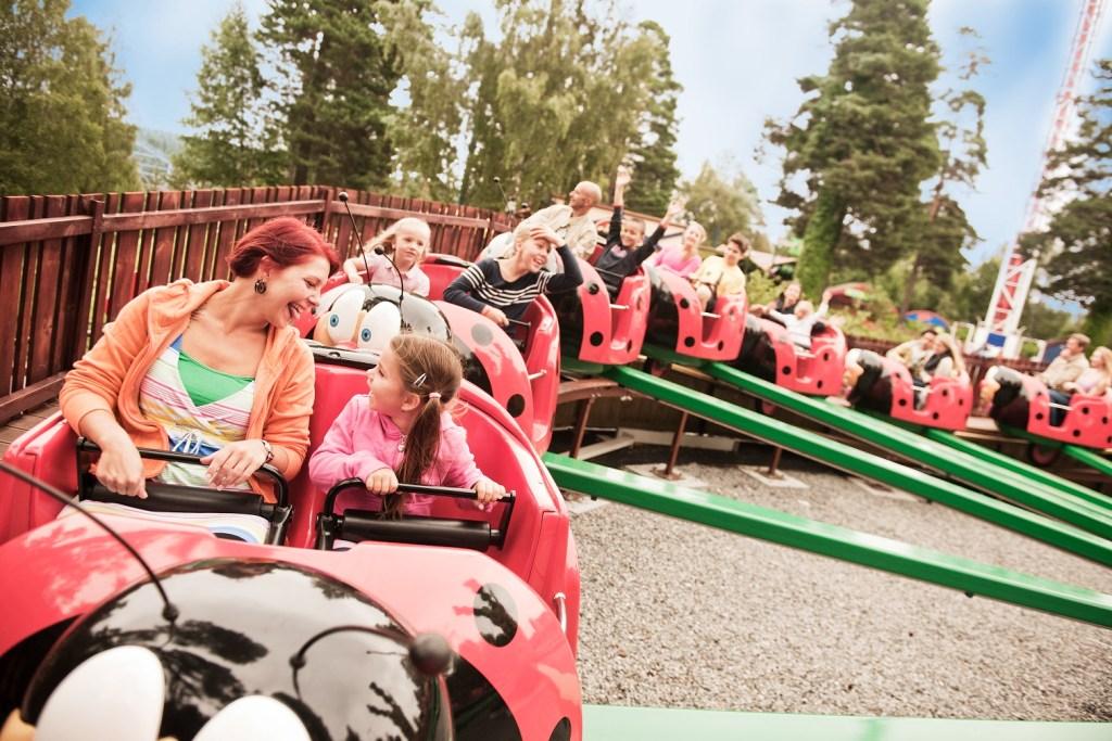 Mor og datter kjører marihøneformet karusell på Tusenfryd utenfor Oslo.