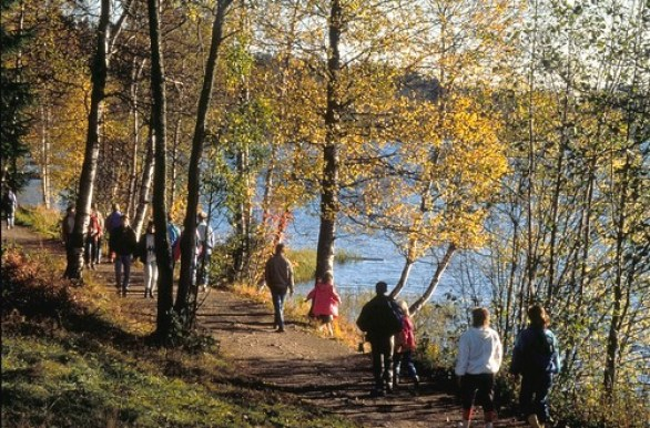 Mange mennesker går tur langs et vann i Nordmarka i Oslo.