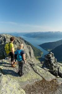 To personer beundrer utsikten over Sognefjorden. Stedet er Keipen i Balestrand. Steinvarde litt i bakgrunnen.