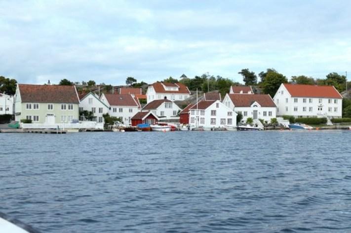 Hvite Sørlandshus i Blindleia utenfor Lillesand. Blå himmel og lette krusninger på vannet.