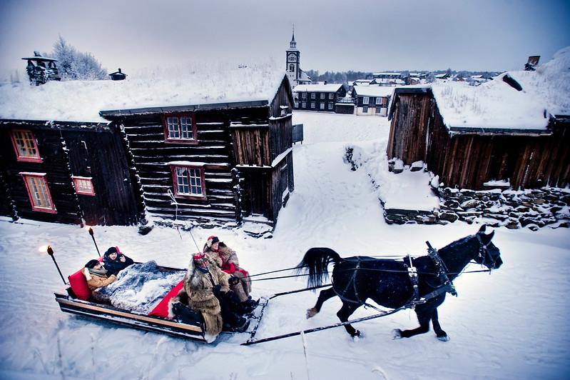 Hest og slede kjører gjennom de snedekte gatene i Røros. Fire personer kledd i pels sitter i sleden. Det er julestemning.