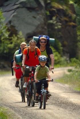 Familie på fire på sykkeltur i Nordmarka. Grusvei og sekker på ryggen. Klare for overnatting.