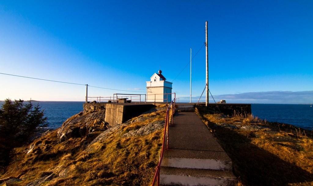 Ryvarden fyr ligger vakert ut mot havet nord for Haugesund. Blå himmel og stille hav.