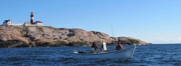 Hvitmalt båt med fyrtårn i bakgrunnen. Blanke svaberg og blå himmel.
