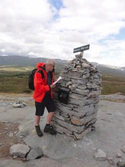 Mann i rød vindjakke ved varden på toppen av Falkenuten i Rauland i Telemark.