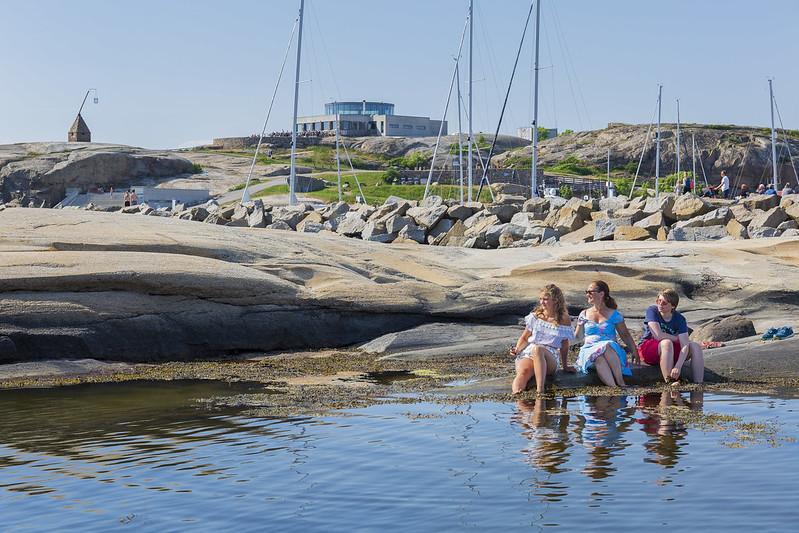 Tre damer sitter med bena i sjøen på et svaberg på Verdens Ende. Vippefyret og restauranten i bakgrunnen.