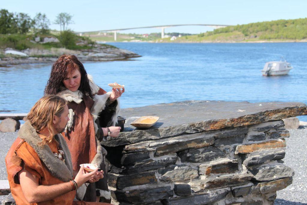 Et steinalderpar spiser mat laget etter urmetoder med Saltstraumen i bakgrunnen.