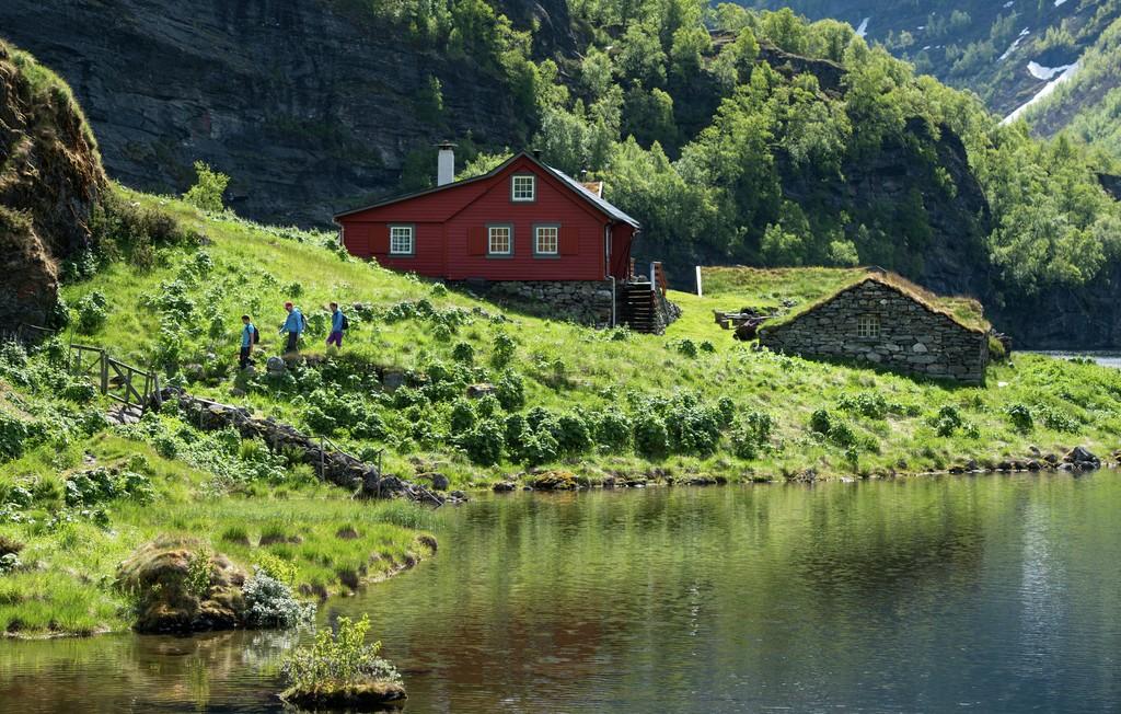 Tre vandrere går gjennom en gård i Aurlandsdalen. Nærmer seg en grind i et gjerde.