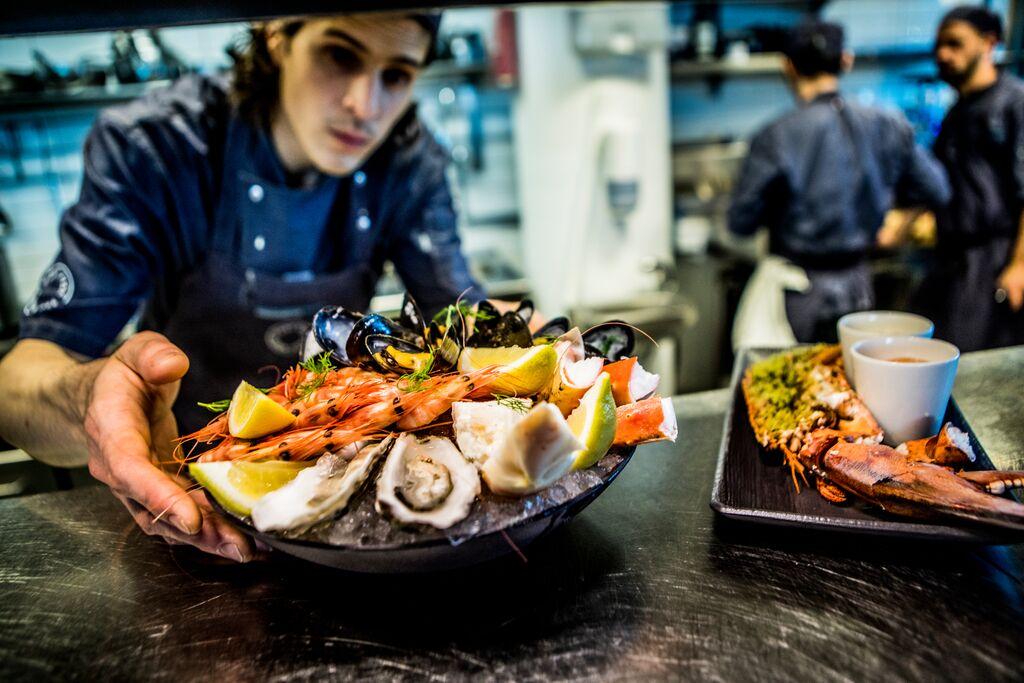 Servitør presenterer et delikat fat med norske skalldyr.