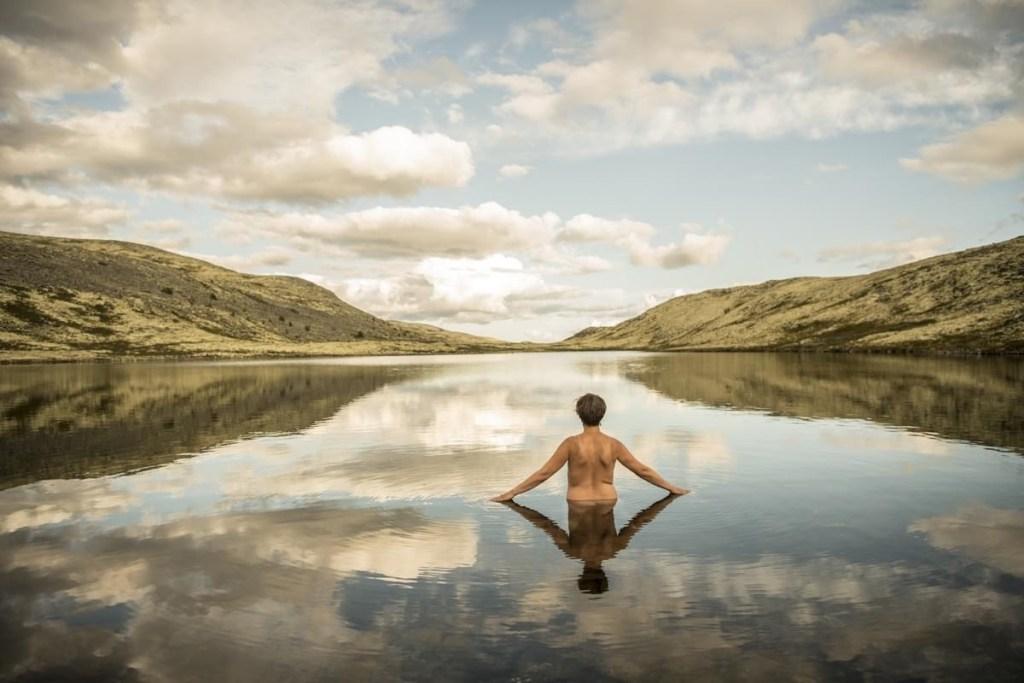 Naken mann sett bakfra på vei ut for å bade i et fjellvann.
