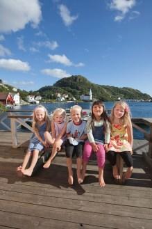 Fem barn sitter på en benk utenfor Isbua på øye Hidra utenfor Flekkefjord. Kirken kan skimtes i bakgrunnen.