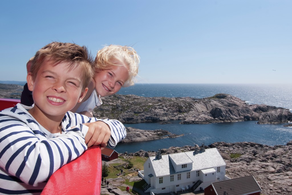 To smilende gutter beundrer utsikten fra toppen av Lindesnes fyr.
