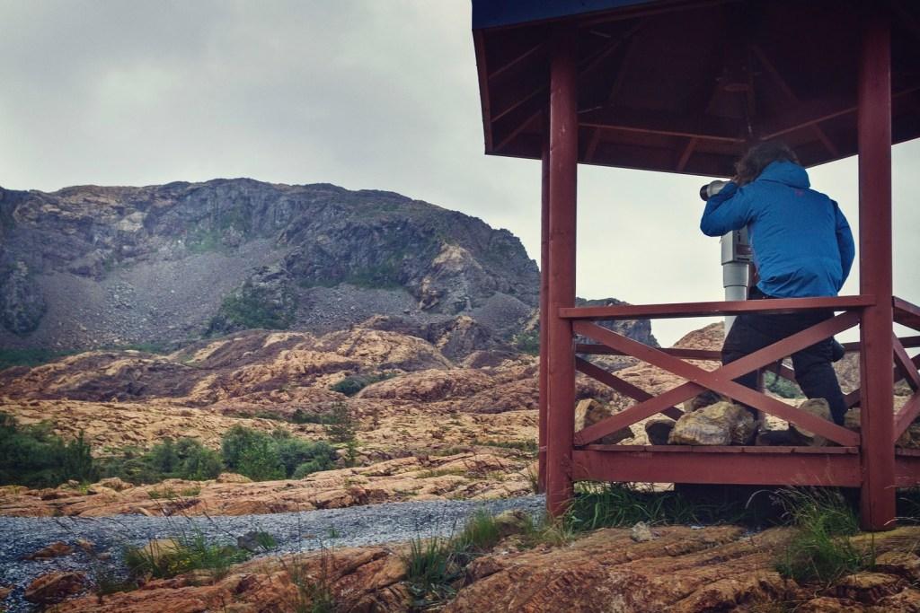 Mann sitter med kikkert får å observerer ørner på øya Leka i Trøndelag.