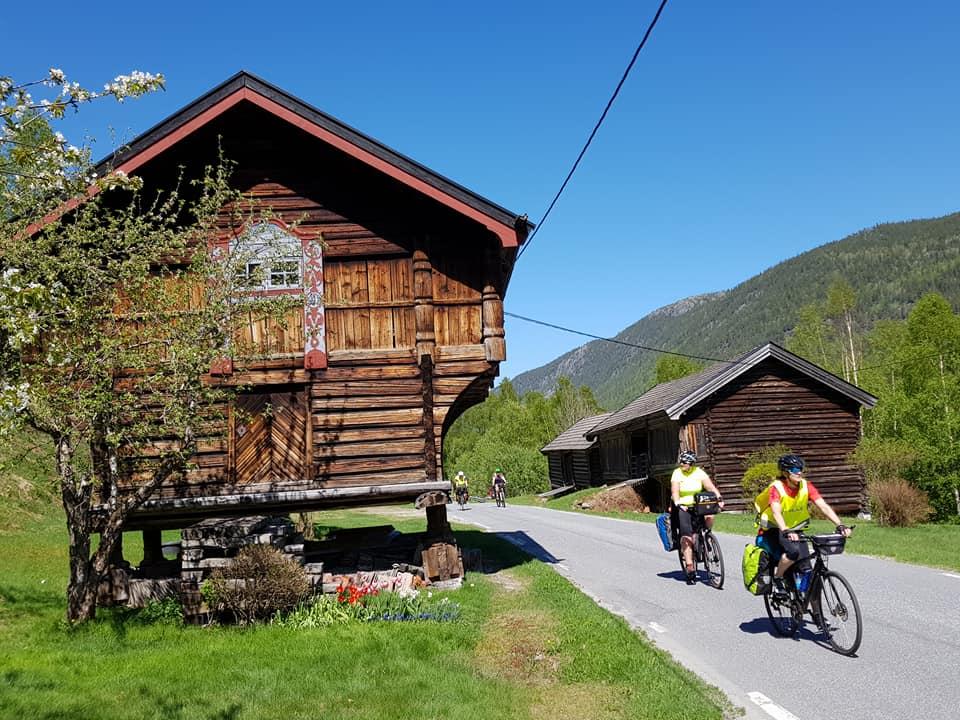Mennesker på sykkeltur passerer et gammelt stabbur langs Numedalsruta.