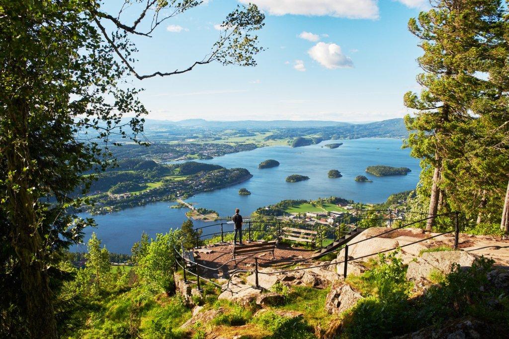 Mann står på utsiktsplattform og nyter utsikten over Tyrifjorden.