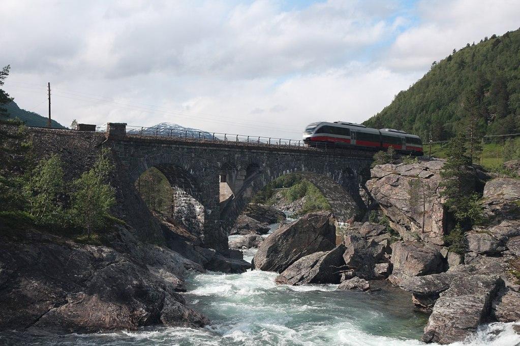 Tog passerer Stuguflåten bru på Raumabanen.