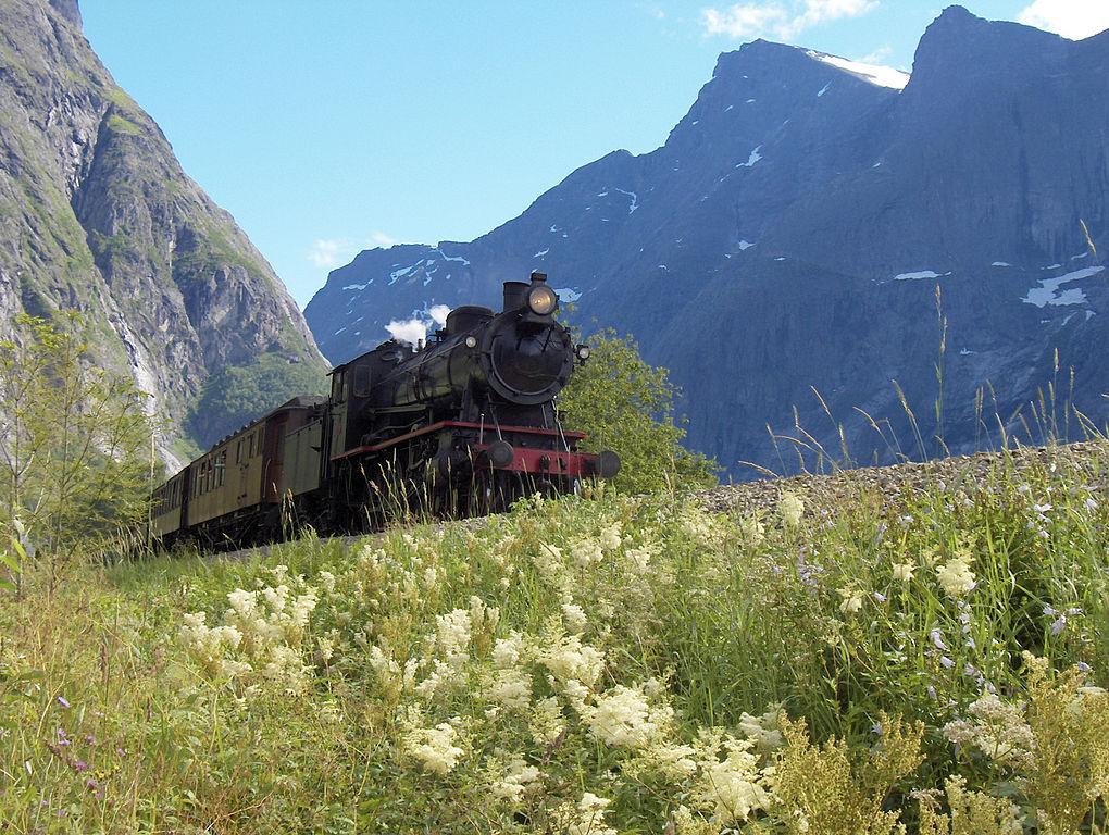 Gammelt damplokomotiv med teakvogner i vakkert landskap gjennom Romsdalen.