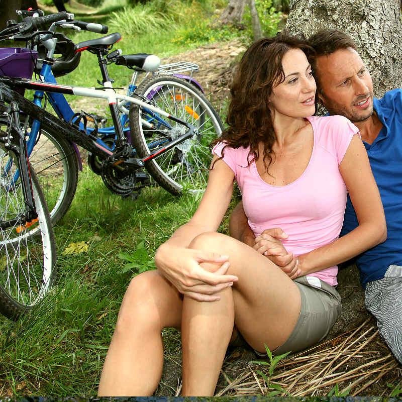 Et yngre par sitter lent opp mot et tre. Tar en pause på sykkelturen.