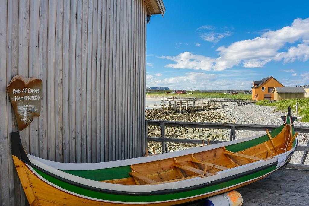 Ny Nordlandsbåt på land med gamle hus i Hamningberg