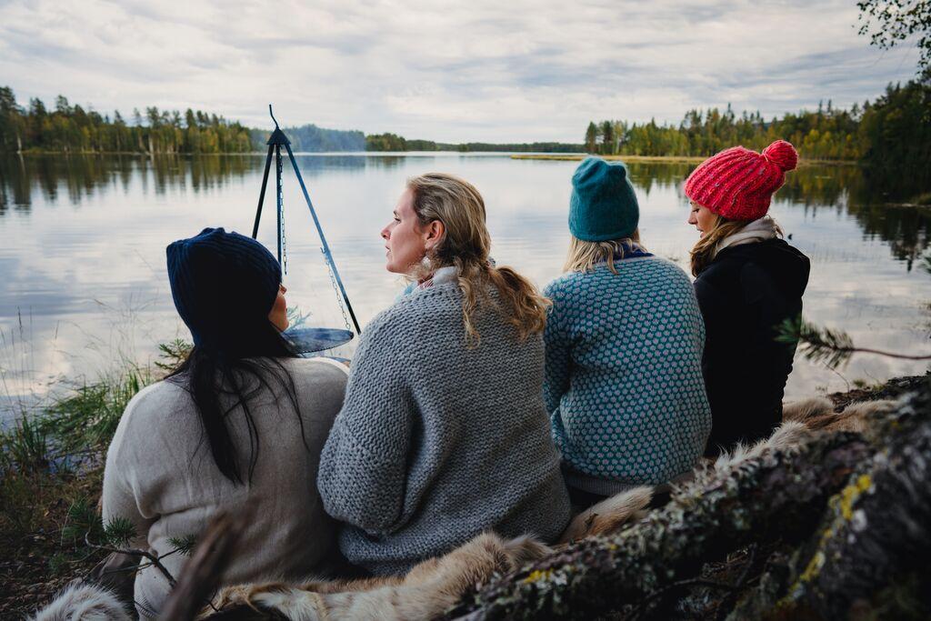 Fire jenter med strikkeluer og strikkegensere sitter å ser ut over en stille innsjø på Finnskogen. Bålpanne og matlaging.