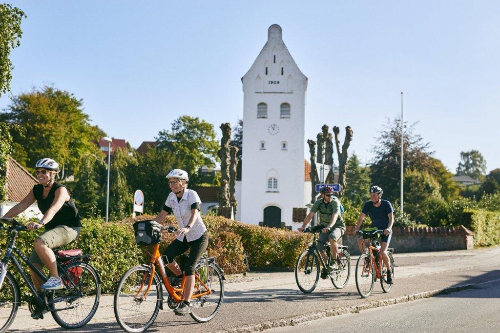 Fire voksne mennesker sykler forbi, alle med hjelm. Gate i danmark.