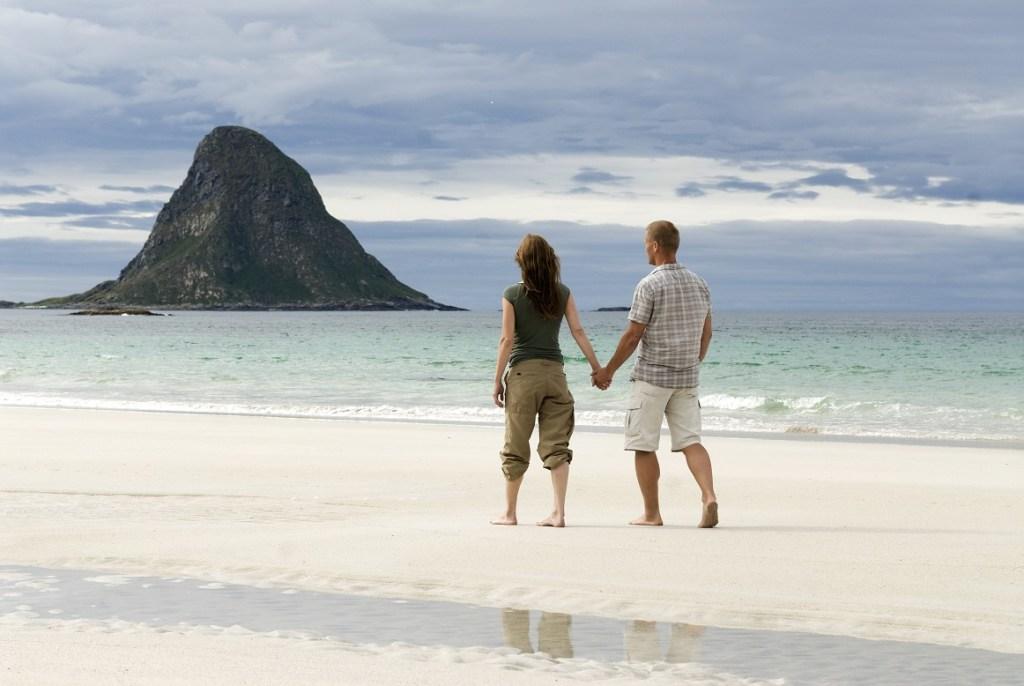 Et par går tur på hvit sandstrand på Bleik på Andøya. Romantisk motiv.