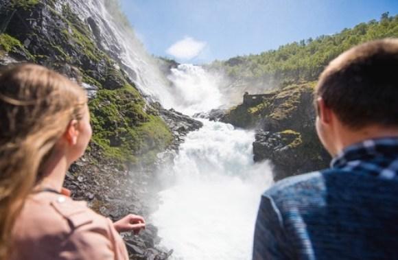 To turister, mann og dame beundrer Kjosfossen på Flåmsbana.