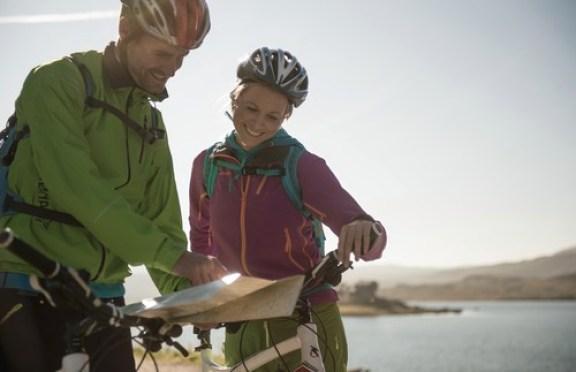 Mann og dame på sykkeltur langs Rallarvegen studerer et kart over sykkelruta.
